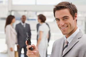 Closeup of happy young businessman text messaging on cellphone with colleagues in the background